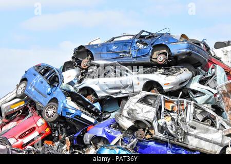 Cars at scrap metal business in recycling scrapyard smashed motor insurance written off car wreck in big heap awaiting crushing London England UK - Stock Photo