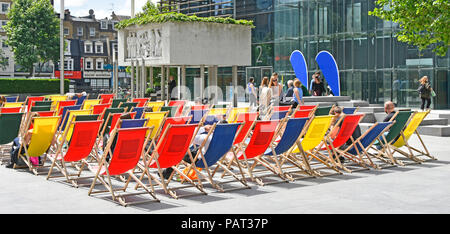 People enjoying sitting in summer sunshine colourful deckchairs outside office block near coffee & food bars just before lunch time London England UK - Stock Photo