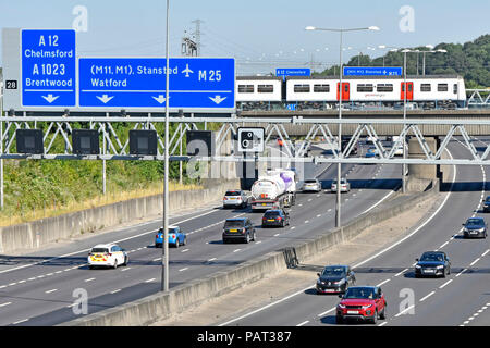 View from above looking down on traffic M25 motorway gantry road sign junction 28 Brentwood Essex Greater Anglia train on railway bridge England UK - Stock Photo