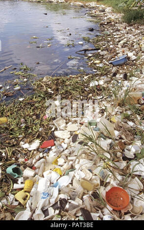 Santo Domingo water side pollution floating plastic packaging waste debris litter garbage junk washed up shoreline Dominican Republic Caribbean Sea - Stock Photo