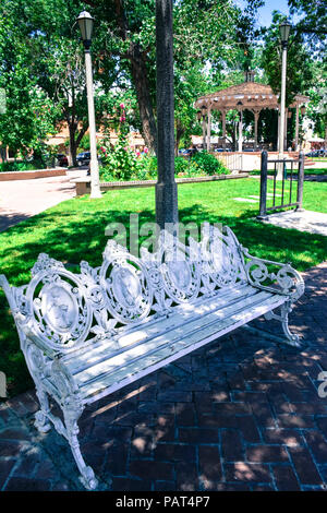 An old fashioned ornate iron scroll work park bench with wooden seat in plaza near gazebo in old town Albuquerque NM - Stock Photo