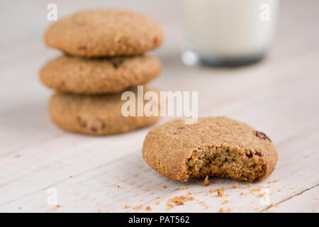 Stacked oats cookies on a wooden background and a glass of milk - Stock Photo