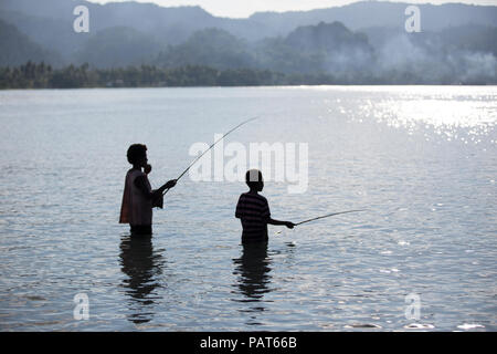Papua New Guinea, Vanimo, silhouette of mother and child fishing in water. - Stock Photo