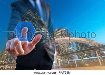 Smart Businessman pose touching virtual technology and night city background - Stock Photo