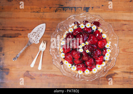 Homemade strawberry cake with red grape juice glaze and daisy flower decoration on old cake stand - Stock Photo