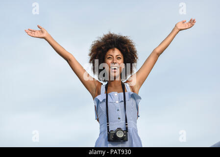 Portrait of happy young woman with camera against sky - Stock Photo