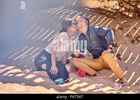 Couple kissing in shadow on the beach - Stock Photo