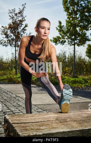 Sportive young woman stretching her leg - Stock Photo