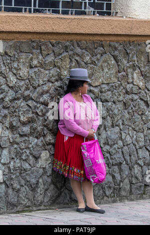 Native Latin woman in pink dress standing on the sidewalk in Ecuador - Stock Photo