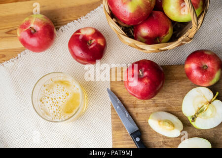 Top view of ripe juicy apples and glass of cidre drink on rustic wooden table. Glass of home made cider and locally grown organic apples, shot from ab - Stock Photo