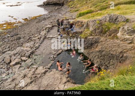 People enjoying a natural hot spring, Flokalundur, West Fjords, Iceland - Stock Photo