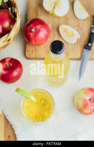Top view cidre bottle on and ripe apples rustic wooden table. Glass and bottle of home made cider and locally grown organic apples, shot from above - Stock Photo