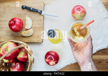 Top view of ripe juicy apples and glass of cidre drink on rustic wooden table. Point of view of hand holding glass of home made cider and locally grow - Stock Photo