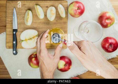 Opening bottle of apple cidre drink, top view. Point of view of hand with can opener, preparing a drink of cider on rustic wooden table with ripe appl - Stock Photo