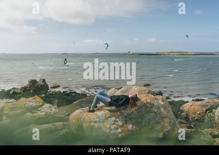 France, Brittany, Landeda, young woman wearing headphones lying on rock at the coast - Stock Photo
