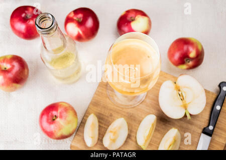 Flat lay with glass of cidre drink on rustic wooden table. Top view of home made cider and locally grown organic apples - Stock Photo