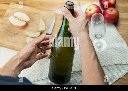 Top view of male hands holding corked bottle of premium cidre. Shot from above with beautiful ice cold bottle of apple wine in man's hands, with local - Stock Photo