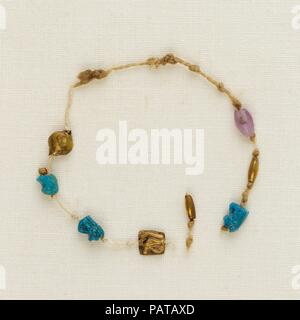 Bracelet with 4 wedjat eyes, 2 barrel beads, and 1 acacia bead. Dimensions: Diam. ca. 3.8 cm (1 1/2 in.). Dynasty: late Dynasty 21. Date: ca. 1000-945 B.C..  One of five bracelets found around the right wrist of Henettawy's mummy, this is a single strand of thin cord. Strung at intervals along the strand were  four wedjat eye amulets, three of faience and one of gold; one gold and one amethyst barrel bead; and one gold acacia bead. The cord was broken, so the original order of the beads and amulets is uncertain.  The wedjat eyes  represent the healed eye of the falcon-god Horus, a powerful sym
