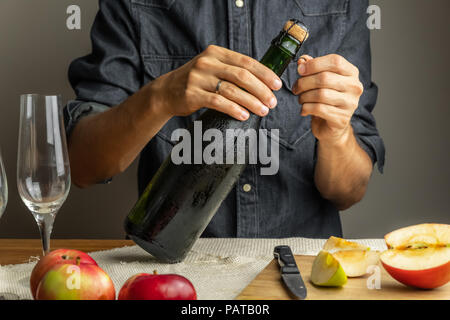 Male hands opening bottle of premium cidre. Uncorking beautiful ice cold bottle of apple wine, with ripe apples in background - Stock Photo