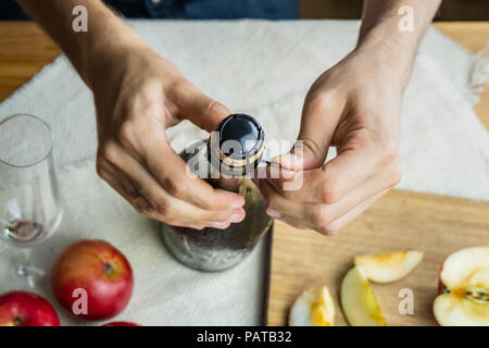 Top view of male hands opening bottle of premium cidre. Shot from above of uncorking beautiful ice cold bottle of apple wine, locally grown ripe apple - Stock Photo