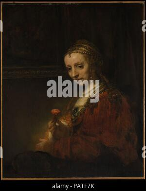Woman with a Pink. Artist: Rembrandt (Rembrandt van Rijn) (Dutch, Leiden 1606-1669 Amsterdam). Dimensions: 36 1/4 x 29 3/8 in. (92.1 x 74.6 cm). Date: early 1660s.  Wearing a romantically outdated costume and exotic jewelry, the woman holds a pink, or carnation, symbol of love and marriage. If the sitter in the pendant portrait, <i>Man with a Magnifying Glass</i> (14.40.621) is Pieter Haringh, then the modestly smiling woman is his wife, Elizabeth Delft (ca. 1620-1679). About a decade earlier the same couple, in conventional attire, was portrayed by Rembrandt's former pupil Jan Victors (1619-a - Stock Photo