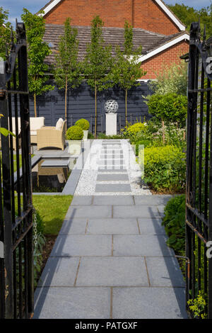 View along London Stone granite path towards focal point of spherical sculpture mounted on a plinth - Stock Photo