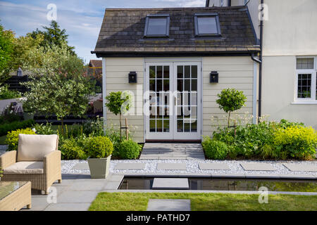 View of house exterior with herbaceous borders, Viburnum tinus topiary and London Stone granite paving - Stock Photo