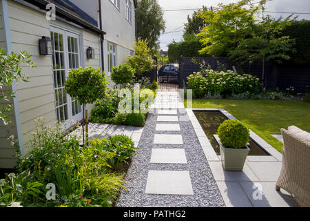 View along London Stone granite paving towards gated entrance, with herbaceous borders, pool water feature and Viburnum tinus topiary - Stock Photo