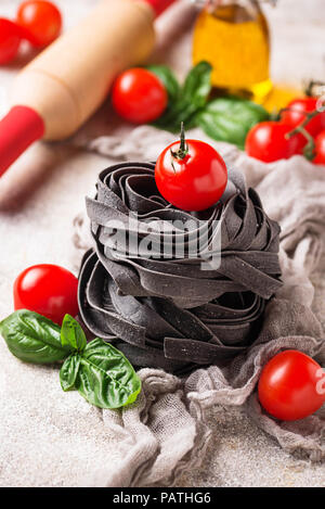 Black uncooked pasta  with tomato and basil - Stock Photo