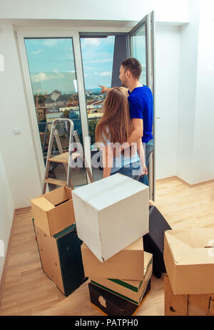 Lovely married couple enjoying in the view of their new apartment - Stock Photo