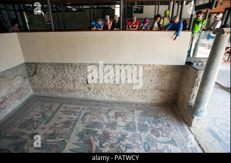 Tourists looking at the 4th century tile mosaics at Villa Romana del Casale, an ancient Roman villa in Sicily, Italy. - Stock Photo