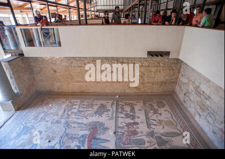 Tourists looking at the 4th century tile mosaics at Villa Romana del Casale, an ancient Roman villa located outside of Piazza Armerina in central Sici - Stock Photo
