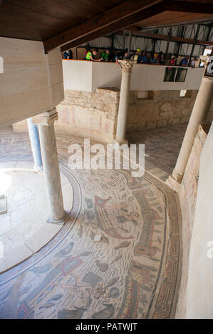 Tourists looking at the 4th century tile mosaics at Villa Romana del Casale, an ancient Roman villa located outside of Piazza Armerina, Sicily. - Stock Photo