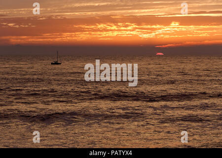Orange seascape with beautiful cloudy sky at sunset with a small sailig boat passing by. Autumn. North of Portugal. - Stock Photo