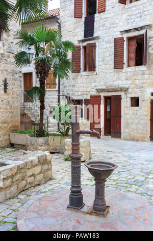 vintage drinking fountain in medieval stone town. stone houses with wooden shutters - Stock Photo
