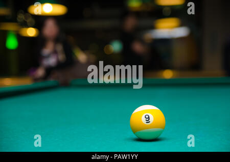 Billiard 9 ball on the pool table against a nice blurred background. - Stock Photo