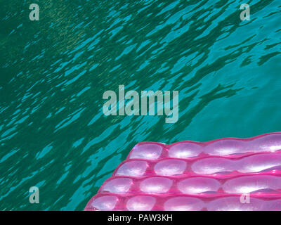 Detail of a pink  inflatable pad (mattress) with water drops on the surface floats  in blue green  transparent sea water - Stock Photo
