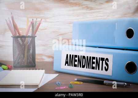Amendments. Office Binder on Wooden Desk. On the table colored pencils, pen, notebook paper - Stock Photo