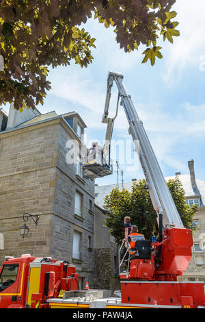 A fireman squad is practicing on an aerial platform truck to reach the upper floor of a building in the walled city of Saint-Malo, France. - Stock Photo