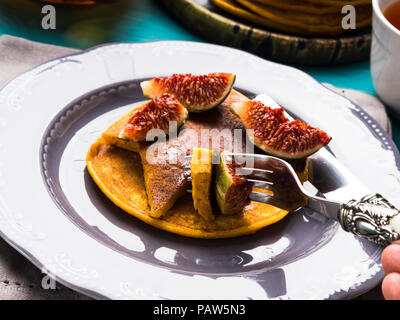 Eating pumpkin pancakes with figs and honey with hot tea. Autumn food background on green wooden table - Stock Photo