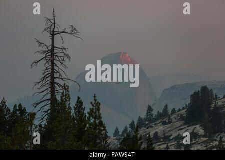 Yosemite National Park, California, USA. 24th July, 2018. Tuesday, July 24, 2018.A last bit of sunlight is reflected off Yosemite National Park's iconic granite feature, Half Dome, as seen from the Olmsted Point vista lookout. Half Dome is enshrouded in smoke from the Ferguson Fire, burning near the park's El Portal entrance. Credit: Tracy Barbutes/ZUMA Wire/Alamy Live News - Stock Photo