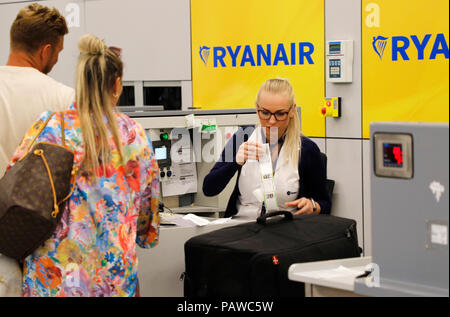 Mallorca, Spain.  25 July 2018, Mallorca, Spain: Airport employee attaches a luggage tag to a Ryanair check-in counter at Palma de Mallorca airport. The start of a two-day strike by cabin crew at the low-cost airline Ryanair has caused great displeasure among countless travellers in several European countries. The most cancellations occurred in Spain, where Ryanair cancelled 200 flights - just under a quarter of all connections. Credit: dpa picture alliance/Alamy Live News - Stock Photo
