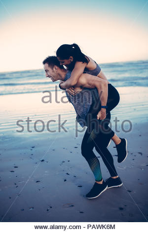 Fit adult couple doing piggyback on a beach - Stock Photo