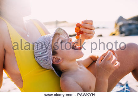 Cute happy little boy eating grapes at the beach - Stock Photo