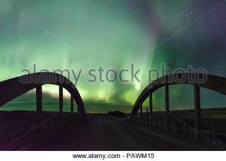 Scenic nature scene of a bridge under an illuminated night sky - Stock Photo