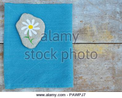 Daisy painted on rock with blue napkin and wood background - Stock Photo