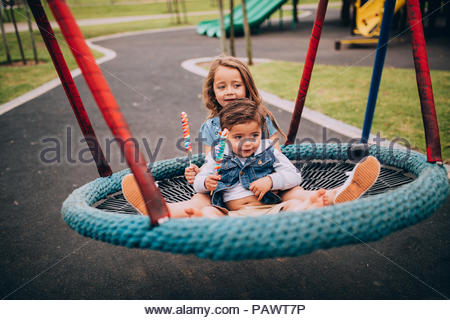 Children playing on a swing in the park - Stock Photo