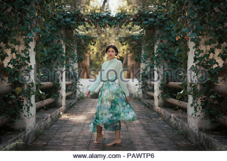 Barefoot woman wearing romantic clothes in pretty garden - Stock Photo