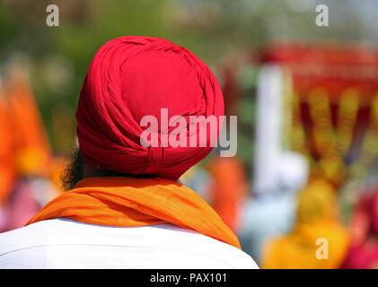 old sikh man with red turban on his head during a religious ceremony. The turban is very important religiuous symbol for this indian culture - Stock Photo