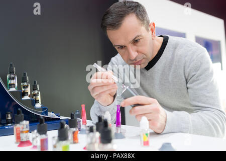 handsome man preparing electronic cigarette for a client - Stock Photo